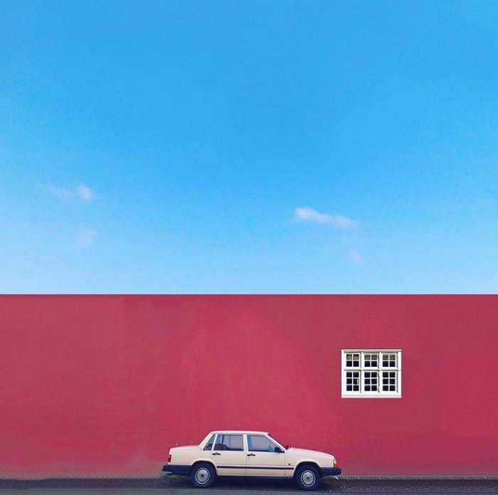 color in photography: an old Volvo parked in front of a red wall with a contrasting cool blue sky above it