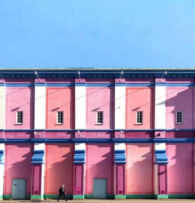 color in photoraphy: a building painted in pink and reds contrast with the cool blue sky above it