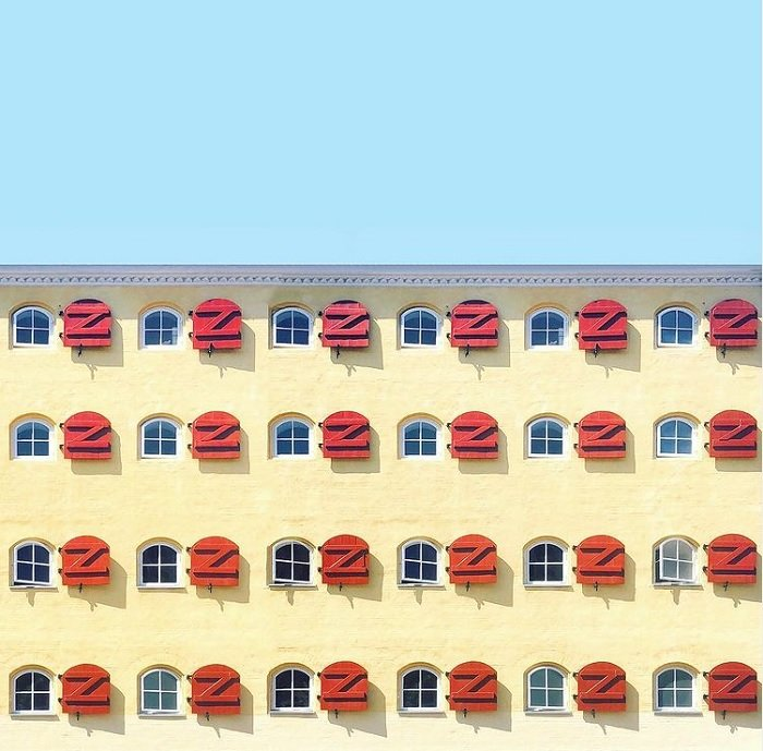 color in photography: a repetitive pattern of windows on a yellow building