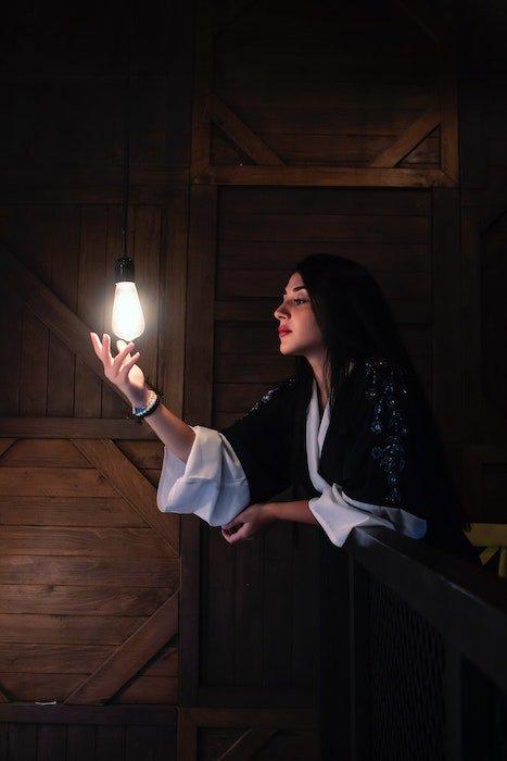 low light photography idea: a single light bulb illuminates a portrait of a woman