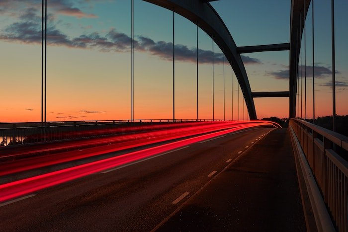 a streak of tail lights over a bridge photographed in low light